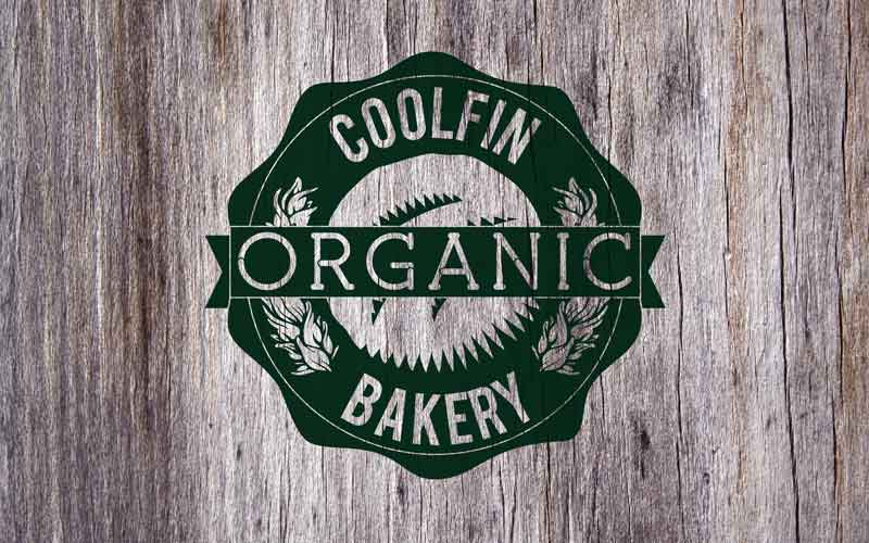 Coolfin Organic Bakery logo on a wood texture background